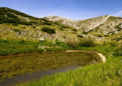 A Babino jezero, szemközt a névadó csúcs, ahol kivehető a túristaút vonala, National park Paklenica, Velebit, Croatia