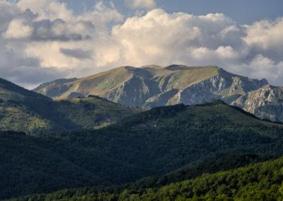Visszanézve: a Bregoč csúcsa, az előtte lévő hegyek oldalában kanyarog az út, Sutjeska National Park, Zelengora, Bosznia-Hercegovina