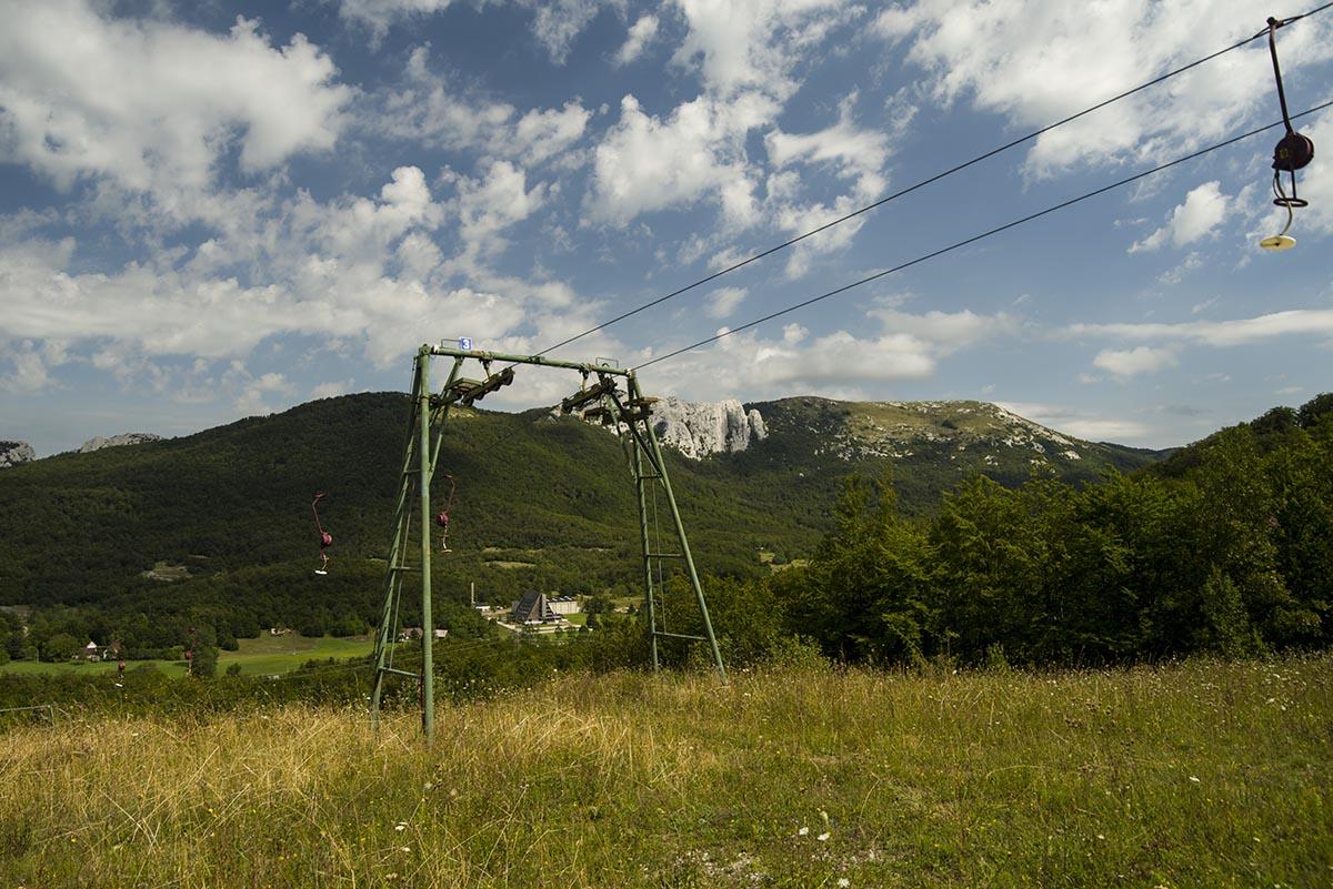 A velebiti sífelvonó, a lábai között a Velebno Hotel, szemben a Ljubičko brdo tömbje